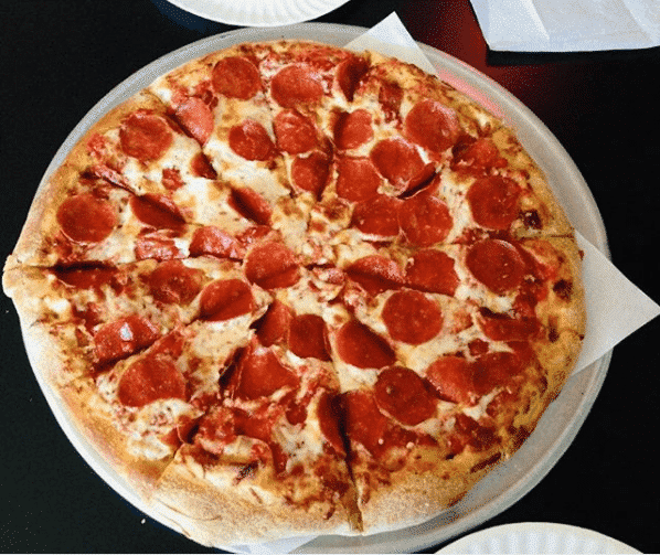 A circular pepperoni pizza cut into 12 slices on a pizza tray.